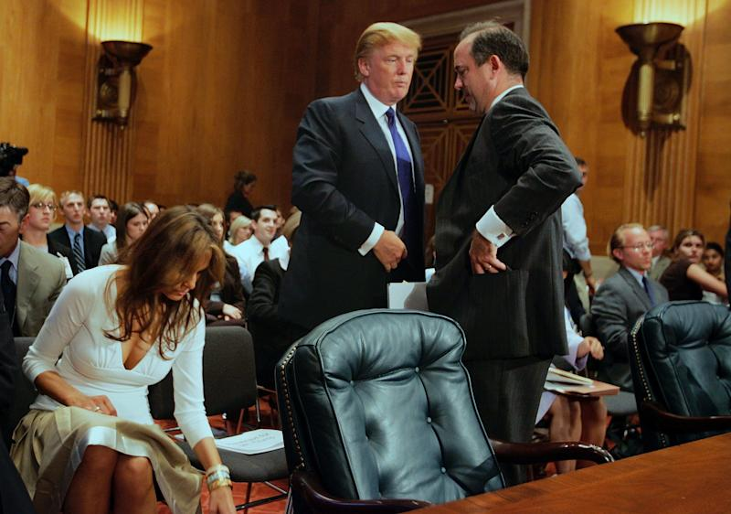 Donald Trump, then president of the Trump Organization, talks to Christopher Burnham, undersecretary general of the U.N. Department of Management, after Trump testified before a Senate Homeland Security and Governmental Affairs subcommittee on July 21, 2005, as his wife, Melania, accompanied him. (Joe Raedle via Getty Images)