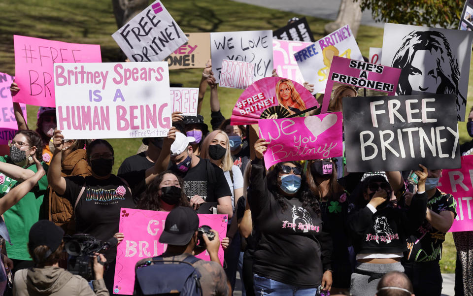 Britney Spears' fans hold signs outside a court hearing concerning the pop singer's conservatorship at the Stanley Mosk Courthouse, March 17, 2021, in Los Angeles. - Credit: AP