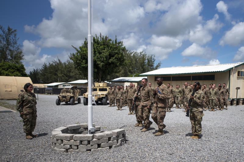 In this photo taken Aug. 26, 2019 and released by the U.S. Air Force, airmen from the 475th Expeditionary Air Base Squadron conduct a flag-raising ceremony, signifying the change from tactical to enduring operations, at Camp Simba, Manda Bay, Kenya. The al-Shabab extremist group said Sunday, Jan. 5, 2020 that it has attacked the Camp Simba military base used by U.S. and Kenyan troops in coastal Kenya, while Kenya's military says the attempted pre-dawn breach was repulsed and at least four attackers were killed. (Staff Sgt. Lexie West/U.S. Air Force via AP)