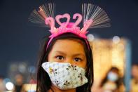 "A girl wearing a mask and ""2021"" head band looks on in Bangkok"