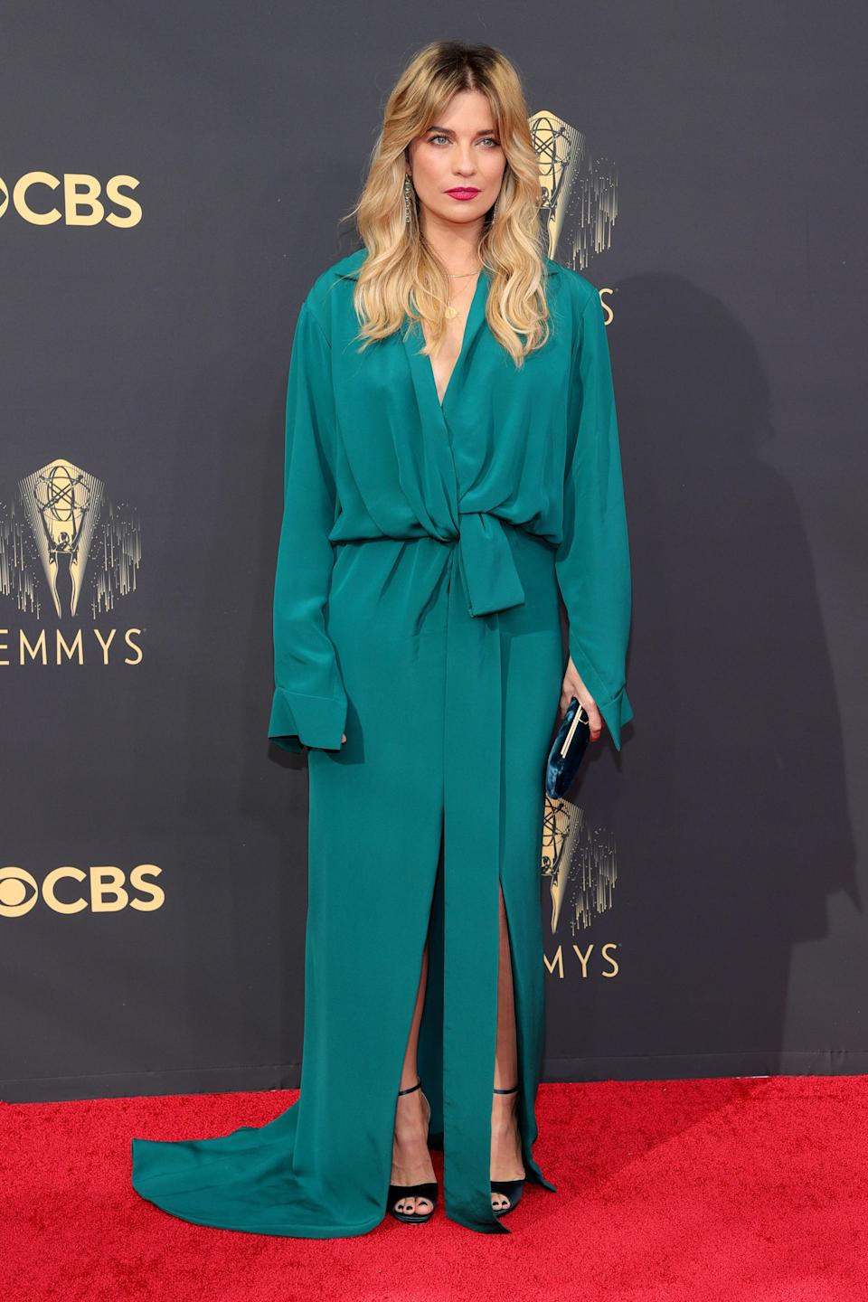 Alexis Rose herself opted for a glamourous teal lounge look from Valentino Couture, pairing it with ankle-strap heels, complementary earrings, and a raspberry lip, plus fluffy blonde waves.