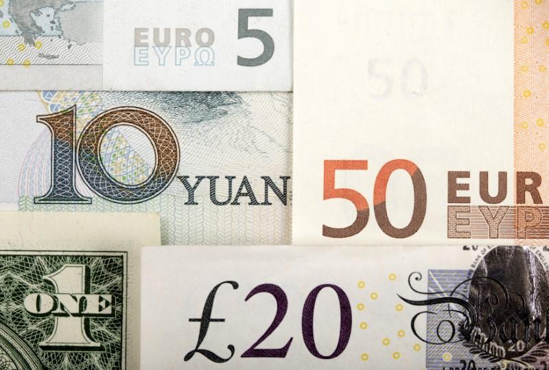 FILE PHOTO: Arrangement of various world currencies including Chinese Yuan, US Dollar, Euro, British Pound