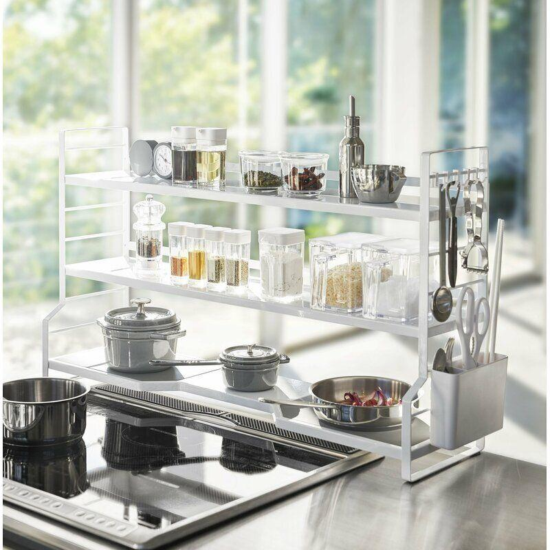 """If you have the right kitchen setup, use <a href=""""https://fave.co/3jxPywo"""" target=""""_blank"""" rel=""""noopener noreferrer"""">this countertop pot rack</a> to create tons of space around your stovetop. This rack includes storage for pots and pans on the bottom (the gray pads double as trivets!), and the top two shelves can be used for lids, spices or whatever else you might need handy. Keep kitchen scissors and utensils within reach with the attached basket on the side. Buy <a href=""""https://amzn.to/35Im4XI"""" target=""""_blank"""" rel=""""noopener noreferrer"""">a few small S-hooks</a>, and you can hang measuring cups, wooden spoons and other gadgets from the sides.<a href=""""https://fave.co/3jxPywo"""" target=""""_blank"""" rel=""""noopener noreferrer"""">Get it for $69 at Wayfair</a>."""
