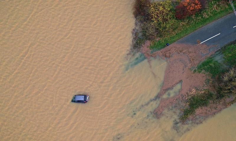 A car is partly submerged in floodwater at Bardney, near Lincoln, after the Barlings Eau broke its banks on 15 November.