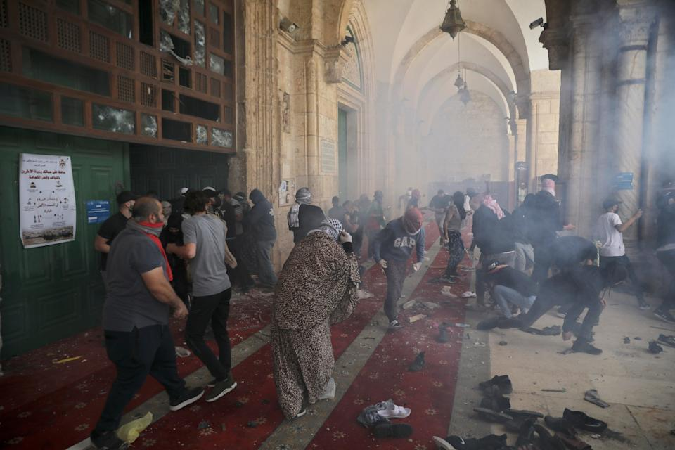 <p>Palestinians clash with Israeli security forces at the al-Aqsa mosque compound on Monday</p> (AP)