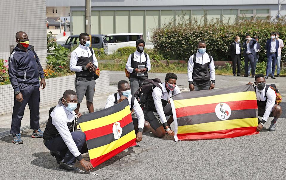 Members of Uganda's Olympic team pose for a photograph upon their arrival at their pre-Olympics camp host town Izumisano, after a member of their team has tested positive fo the coronavirus disease (COVID-19) and was barred entry into Japan, in Izumisano, Osaka prefecture, wetsern Japan June 20, 2021, in this photo taken by Kyodo. Kyodo/via REUTERS ATTENTION EDITORS - THIS IMAGE WAS PROVIDED BY A THIRD PARTY. MANDATORY CREDIT. JAPAN OUT. NO COMMERCIAL OR EDITORIAL SALES IN JAPAN
