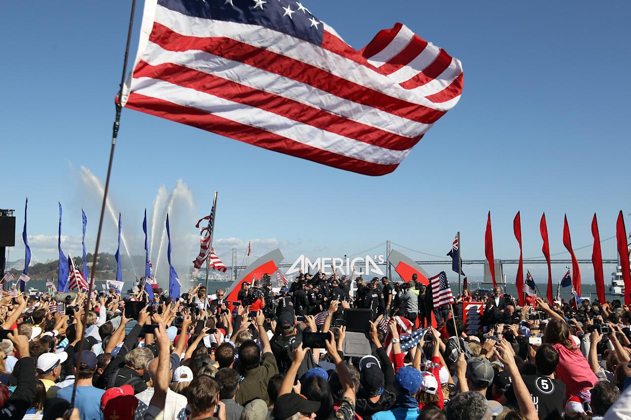 SAN FRANCISCO, CA - SEPTEMBER 25: Oracle Team USA celebrates with the America's Cup trophy after they beat Emirates Team New Zealand skippered by Dean Barker in race 19 to win the America's Cup Finals on September 25, 2013 in San Francisco, California. (Photo by Ezra Shaw/Getty Images)