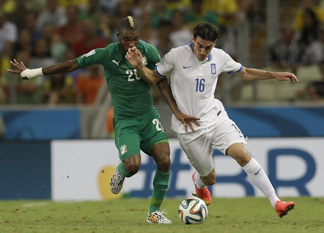 Ivory Coast's Serey Die, left, and Greece's Lazaros Christodoulopoulos challenge for the ball during the group C World Cup soccer match between Greece and Ivory Coast at the Arena Castelao in Fortaleza, Brazil, Tuesday, June 24, 2014. (AP Photo/Natacha Pisarenko)