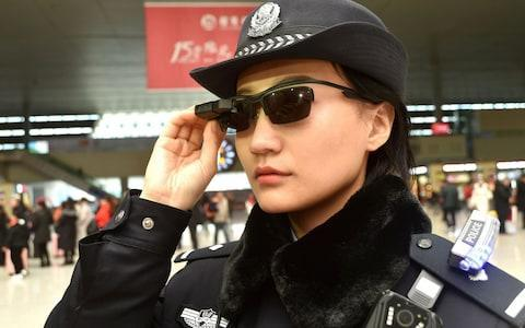 <span>A police officer wearing a pair of smartglasses with a facial recognition system at Zhengzhou East Railway Station, central China</span> <span>Credit: AFP </span>