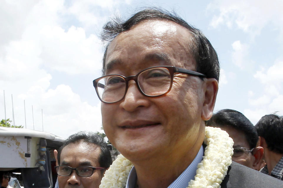 FILE - In this Aug. 16, 2015, file photo, Sam Rainsy, leader of the opposition Cambodia National Rescue Party, greets his party supporters upon his arrival at Phnom Penh International Airport in Phnom Penh, Cambodia. Phnom Penh Municipal Court has convicted and sentenced the exiled leader and senior members of the country's banned opposition party to more than 20 years in prison, effectively barring them from ever returning home. The decision taken by the court late Monday, March 1, 2021 was condemned by the head of the Cambodia National Rescue Party , or CNRP, human rights organizations and the United States embassy. The trial was held in absentia as all the party leaders are living abroad. (AP Photo/Heng Sinith, File)