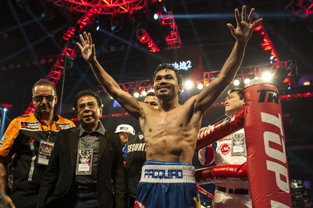 Manny Pacquiao celebrates his victory over Chris Algieri at the end of their world welterweight championship boxing bout in Macau on November 23, 2014 (AFP Photo/Xaume Olleros)