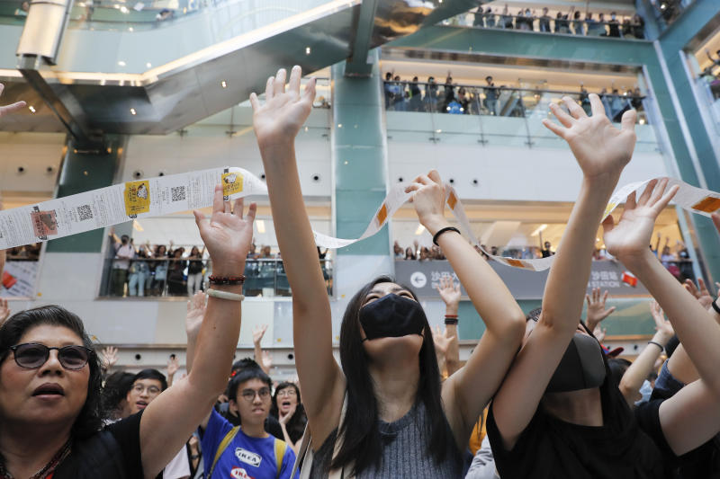 "Protesters grab queuing tickets hanging from several floors above issued by a restaurant owned by a pro-Beijing company inside a shopping mall at the Sha Tin district in Hong Kong Sunday, Sept. 22, 2019. Young protesters, many wearing masks to disguise their identity, filled the open area of a Hong Kong shopping mall Sunday and folded paper ""origami"" cranes in the latest twist in a pro-democracy movement that has stretched into a fourth month. (AP Photo/Kin Cheung)"