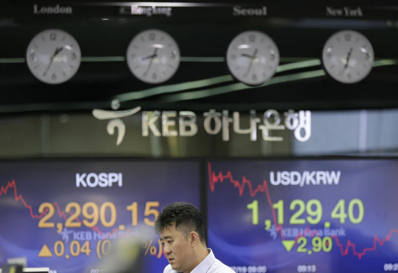 A bank employee stands near screens showing the Korea Composite Stock Price Index (KOSPI), left, and the foreign exchange rate between U.S. dollar and South Korean won at the foreign exchange dealing room in Seoul, South Korea, Thursday, July 19, 2018. Asian stock markets drifted without a clear direction on Thursday while investors wait and see further developments on global trade disputes. (AP Photo/Lee Jin-man)