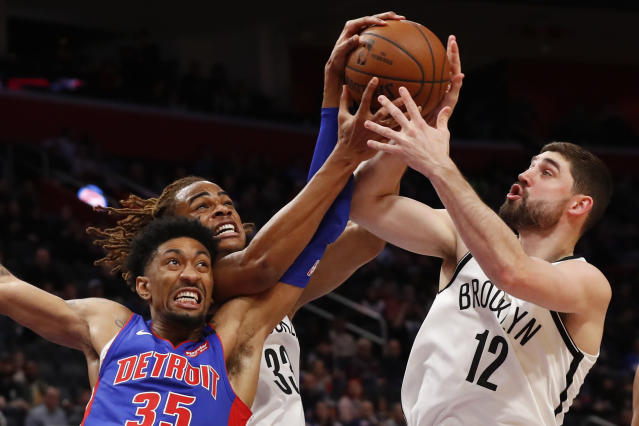 Detroit Pistons forward Christian Wood (35), Brooklyn Nets forward Nicolas Claxton (33) and Joe Harris (12) battle for a rebound in the first half of an NBA basketball game in Detroit, Saturday, Jan. 25, 2020. (AP Photo/Paul Sancya)