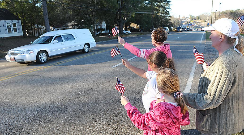 "Residents raise flags along the processional route in Ozark for Dale County Schools bus driver Charles ""Chuck"" Poland Jr., who died Tuesday, in Ozark, Ala., Sunday, Feb. 3, 2013. Authorities say Jim Lee Dykes, 65 — a decorated veteran of the Vietnam War known as Jimmy to neighbors — gunned down Poland, a school bus driver, and then abducted a 5-year-old boy from the bus, taking him to an underground bunker on his rural property. (AP Photo/Dothan Eagle, Danny Tindell)"