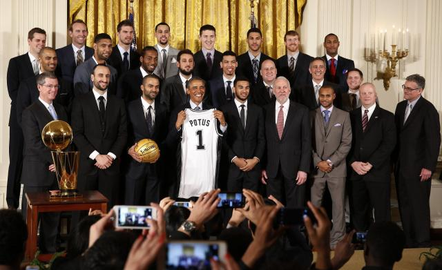 U.S. President Barack Obama poses for a team photo as he welcomes the 2014 NBA Champion San Antonio Spurs to the East Room of the White House in Washington, January 12, 2015. REUTERS/Larry Downing (UNITED STATES - Tags: POLITICS SPORT BASKETBALL)