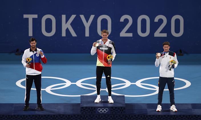 Silver medalist Karen Khachanov of Team ROC, gold medalist Alexander Zverev of Team Germany, and bronze medalist Pablo Carreño Busta of Team Spain pose on the podium during the medal ceremony for the tennis men's singles today at Ariake Tennis Park in Tokyo.