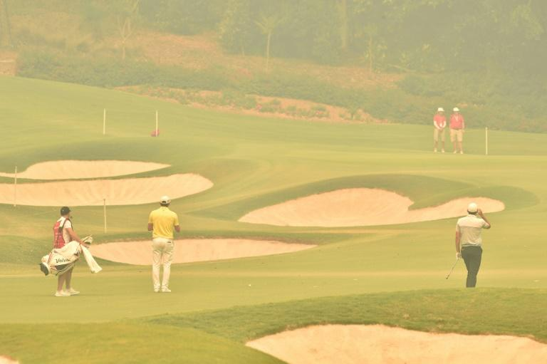 Golfers play through thick haze from bushfires during the first round of the Australian Open in Sydney on December 5 (AFP Photo/PETER PARKS)