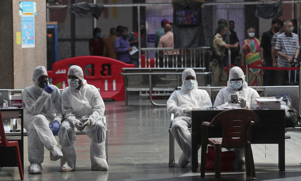 Health workers take a break from taking nasal swab samples from passengers to test for for COVID-19 at a train station in Mumbai, India, Friday, Nov. 27, 2020. India has more than 9 million cases of coronavirus, second behind the United States. (AP Photo/Rafiq Maqbool)