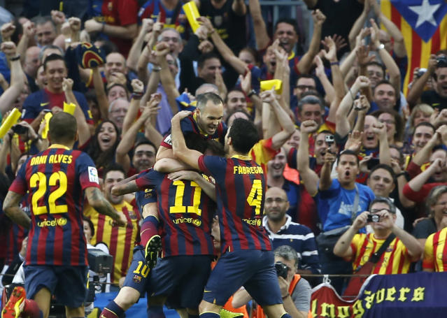 Barcelona's Neymar, centre obscured, celebrates with teammates scoring his side's first goal during a Spanish La Liga soccer match between Barcelona F.C. and Real Madrid at the Camp Nou stadium in Barcelona, Spain, Saturday, Oct. 26, 2013. (AP Photo/Emilio Morenatti)