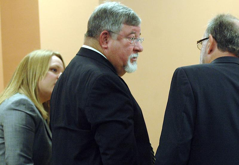 FILE - In this May 20, 2011 file photo, suspended State District Judge Michael Murphy, center, speaks with his defense attorneys Margaret Strickland, left, and Michael Stout during a hearing  in the Third Judicial District Court in Las Cruces, N.M. A change of plea hearing is scheduled for Murphy, the retired Las Cruces judge accused of funneling bribes to former New Mexico Gov. Bill Richardson for judicial appointments. (AP Photo/Las Cruces Sun-News, Robin Zielinski, File)