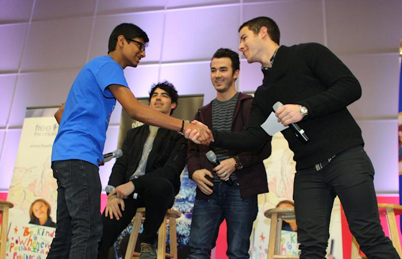 MINNEAPOLIS, MN - FEBRUARY 06: Nick Jonas of the musical trio the Jonas Brothers shakes hands with Siddartha Paari after surprising 600 students at Minneapolis Patrick Henry High School to launch 'We Day' on February 6, 2013 in Minneapolis, Minnesota. (Photo by Adam Bettcher/Getty Images for Free The Children)