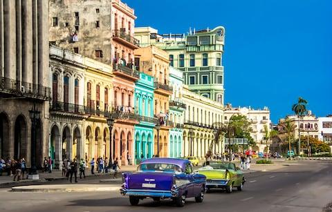 View of old cars and buildings in Havana, Cuba - Credit: Getty