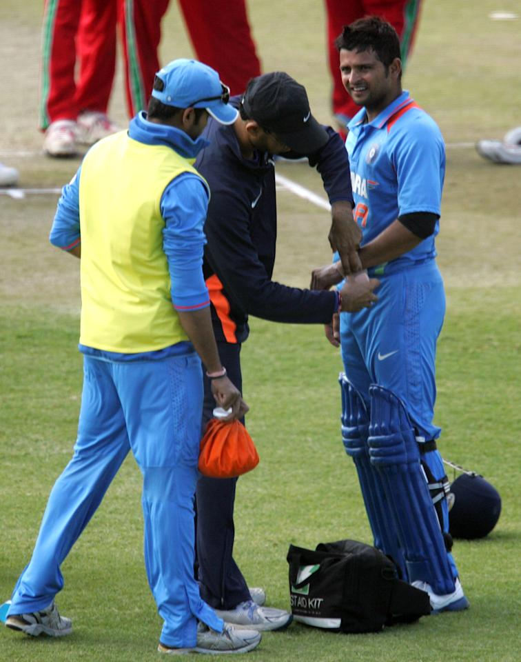 Indian batsman Suresh Raina (R) has his wrist attended to during the 4th match of the 5-match cricket ODI series between Zimbabwe and India at Queen's Sports Club in Harare on August 1, 2013. AFP/PHOTO Jekesai Njikizana        (Photo credit should read JEKESAI NJIKIZANA/AFP/Getty Images)