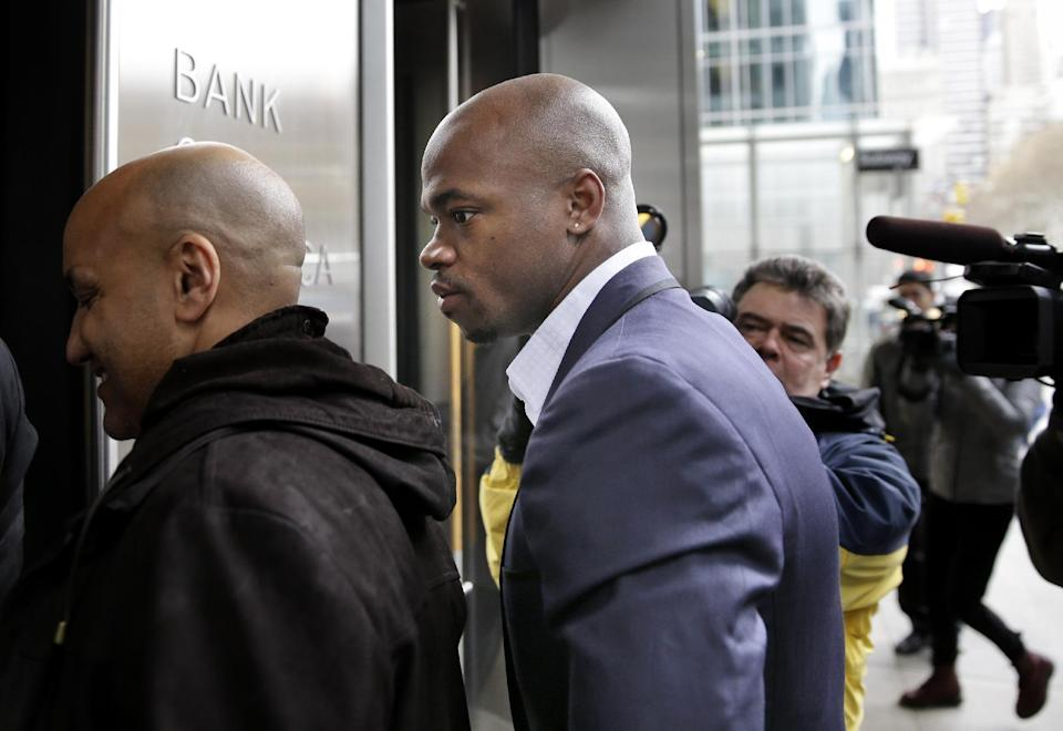 Minnesota Vikings' Adrian Peterson, right, arrives for a hearing for the appeal of his suspension in New York, Tuesday, Dec. 2, 2014. (AP Photo/Seth Wenig)