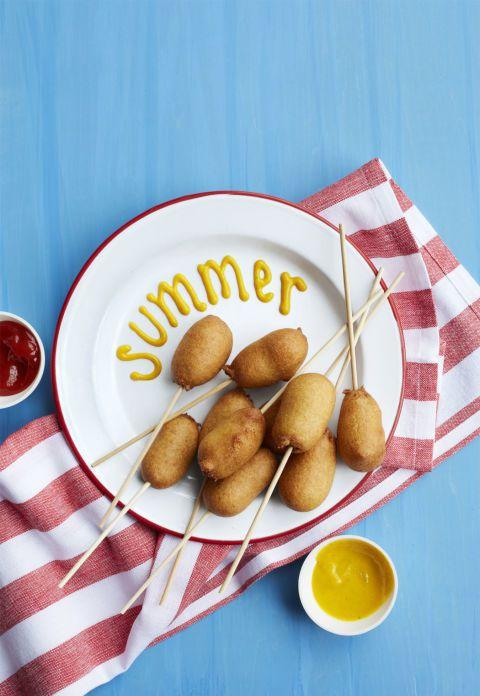"""<p>These bite-size corn dogs make the perfect party appetizer. </p><p><strong><a rel=""""nofollow"""" href=""""https://www.womansday.com/food-recipes/food-drinks/recipes/a55352/corn-pups-recipe/"""">Get the recipe.</a></strong></p>"""