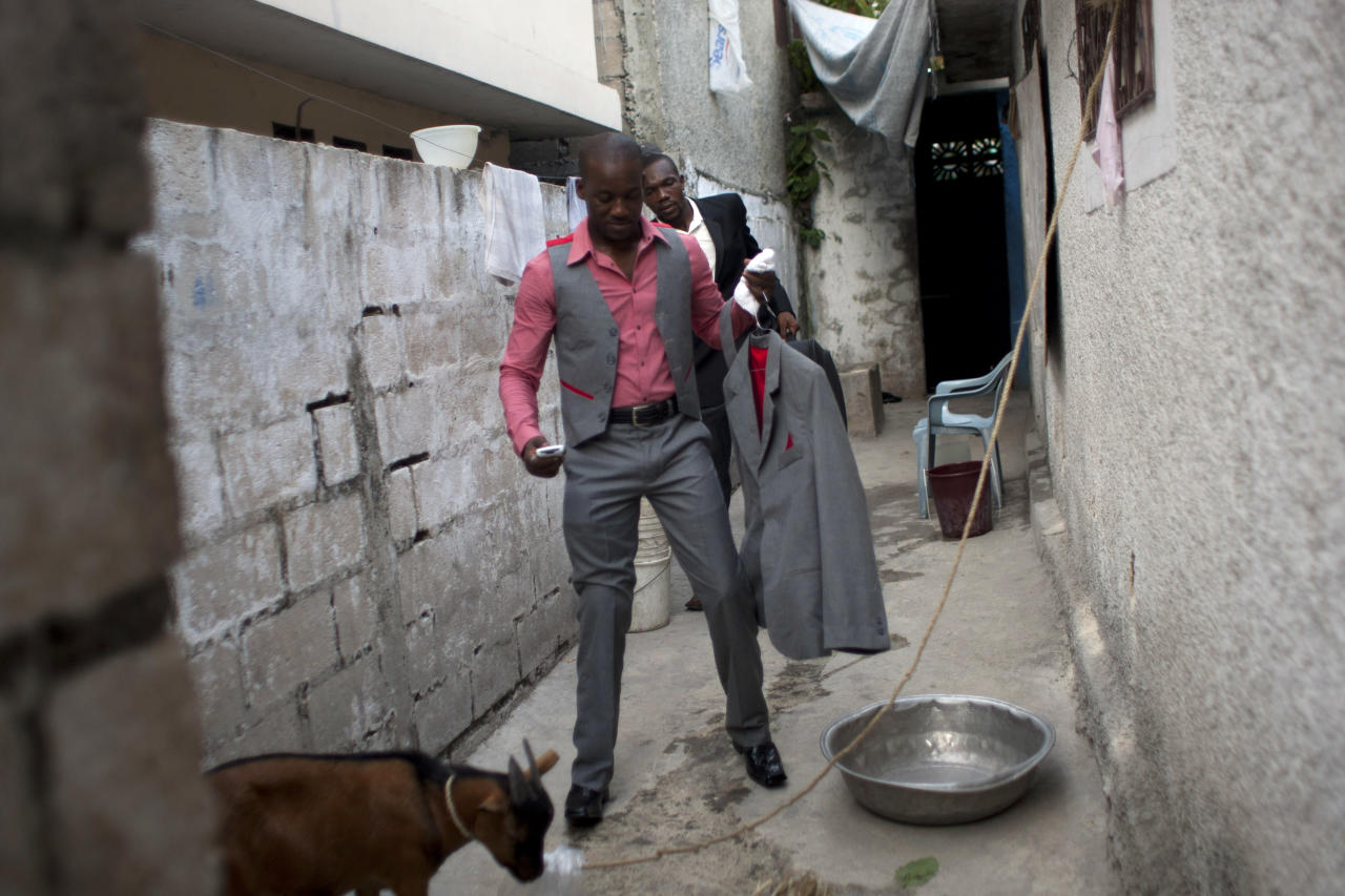 In this July 20, 2012 photo, professional dancer Georges Exantus walks out of his home to his wedding ceremony in Port-au-Prince, Haiti. Georges Exantus thought he'd never dance again. The earthquake three years ago in Haiti's capital flattened the apartment where he was living and he spent three days trapped under a heap of jagged rubble. After friends dug him out, doctors amputated his right leg just below the knee. Exantus walks with a slight limp and he can't dance as fast as he used to or balance as well or do some of his old moves, such as flipping his partner over his shoulder. (AP Photo/Dieu Nalio Chery)