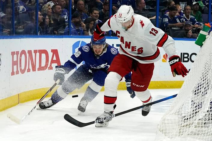 Carolina Hurricanes left wing Warren Foegele (13) loses his stick as he moves the puck in front of Tampa Bay Lightning defenseman Mikhail Sergachev (98) during the first period in Game 4 of an NHL hockey Stanley Cup second-round playoff series Saturday, June 5, 2021, in Tampa.