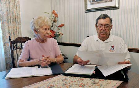 Retired engineer Bill Jenkins and his wife Carol look over documents concerning their investment in Reef's Income & Development Fund II at their home in Orlando, Florida, October 31, 2014. REUTERS/Steve Nesius