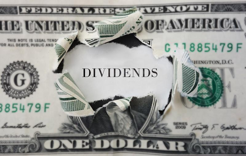 The word DIVIDENDS poking through hole in dollar bill