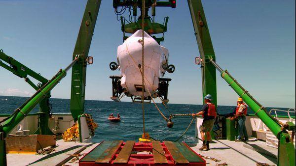The Pisces IV submersible is lifted into the water.
