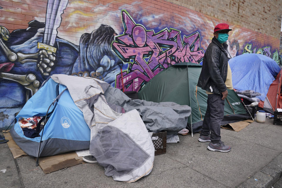 """Sotero Cirilo stands near the tent, left, where he sleeps next to other homeless people in the Queens borough of New York, Wednesday, April 14, 2021. The 55-year-old immigrant from Mexico used to make $800 per week at two Manhattan restaurants, which closed when the COVID-19 pandemic started. A few months later, he couldn't afford the rent of his Bronx room, and afterward, of another room in Queens he moved into. """"I never thought I would end up like this, like I am today,"""" he said, his eyes filling up with tears. (AP Photo/Seth Wenig)"""