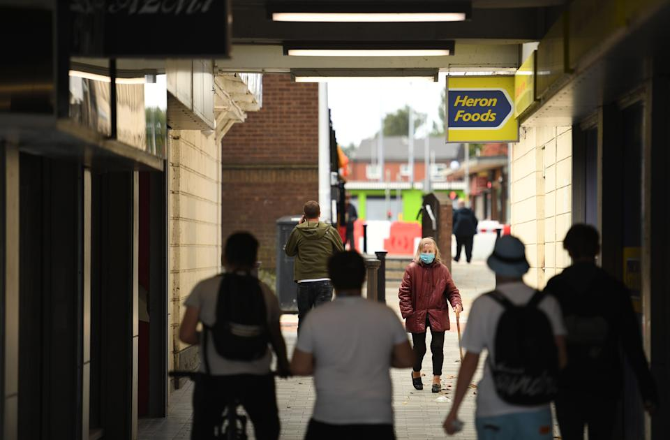 """People wear face masks as a precaution against the transmission of COVID-19 as they walk past closed shops in the centre of Bolton, northern England on September 9, 2020, as local lockdown restrictions are put in place due to a spike in cases of the novel coronavirus in the city. - The UK government, which controls health policy in England, imposed tougher restrictions on Bolton, near the northwest city of Manchester, after a """"very significant rise"""" in cases. Bolton was found to have 120 cases per 100,000 people -- the highest in the country. (Photo by Oli SCARFF / AFP) (Photo by OLI SCARFF/AFP via Getty Images)"""