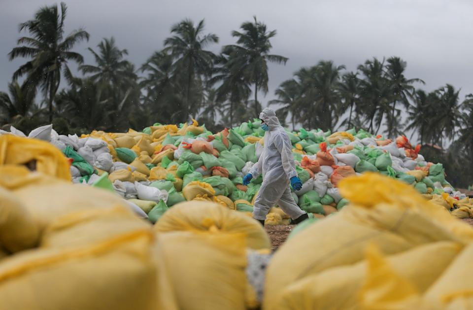 A Sri Lankan navy member walks past the sacks of collected debris washed to a beach from the MV X-Press Pearl container ship which caught fire and sunk off the Colombo Harbour, in Ja-Ela, Sri Lanka June 14, 2021. REUTERS/Dinuka Liyanawatte     TPX IMAGES OF THE DAY