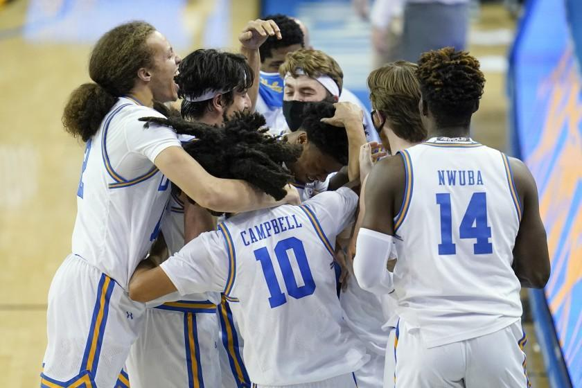 UCLA players celebrate after guard Jaylen Clark, center, made a free throw to give UCLA the lead.