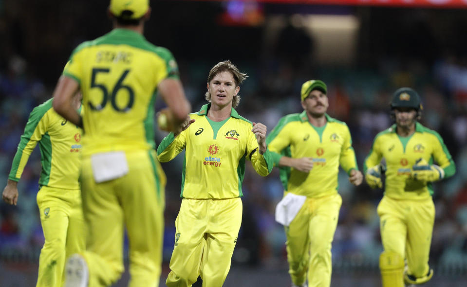 Australia's Adam Zampa, centre, runs to teammate Australia's Mitchell Starc after taking the wicket of India's Hardik Pandya during the one day international cricket match between India and Australia at the Sydney Cricket Ground in Sydney, Australia, Friday, Nov. 27, 2020. (AP Photo/Rick Rycroft)
