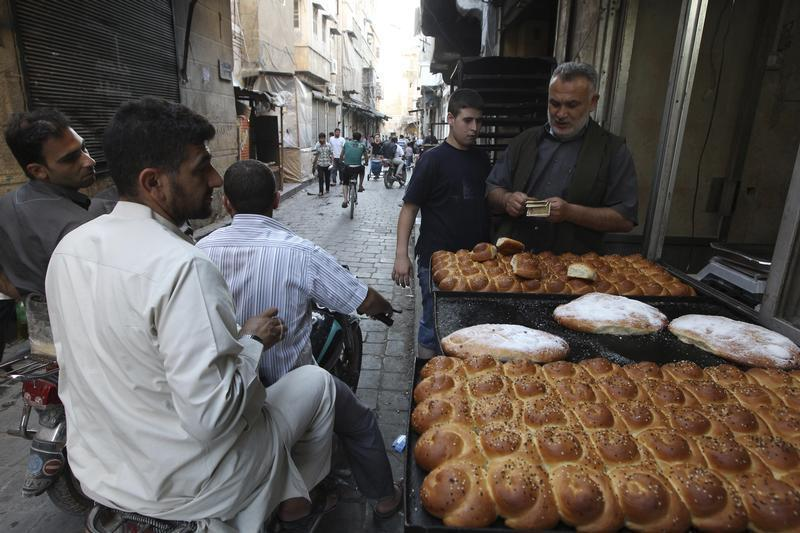 A street vendor sells traditional bread before the time for iftar, or breaking fast, during the Muslim fasting month of Ramadan in Aleppo