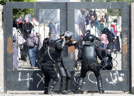 Riot police attempt to break open the entrance of the al-Azhar University Campus during clashes in Cairo