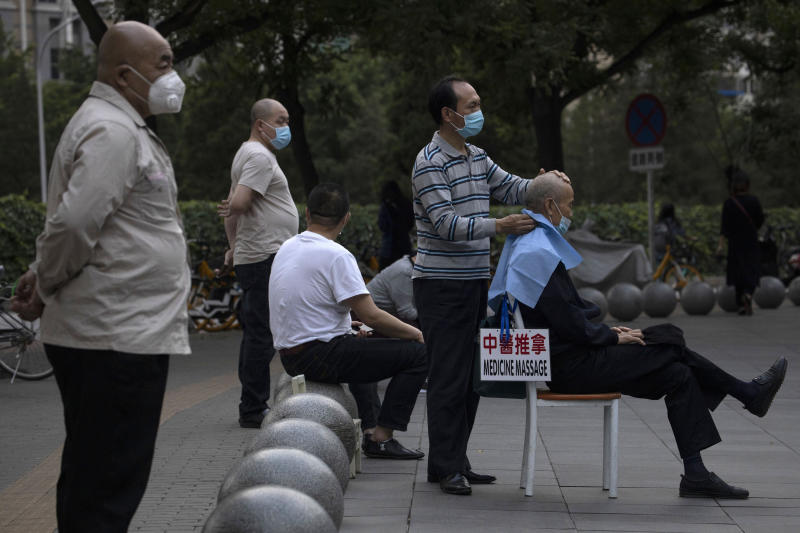 A masseur wearing a mask to curb the spread of the new coronavirus gives a customer a massage a shopping mall in Beijing on Monday, May 25, 2020. (AP Photo/Ng Han Guan)