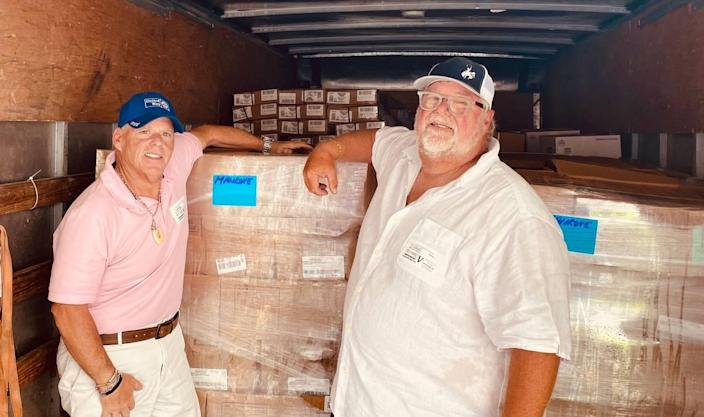 Mike Forster and Michael Rempe stand inside a truck containing donated meat from Cargill Protein in April 2020.