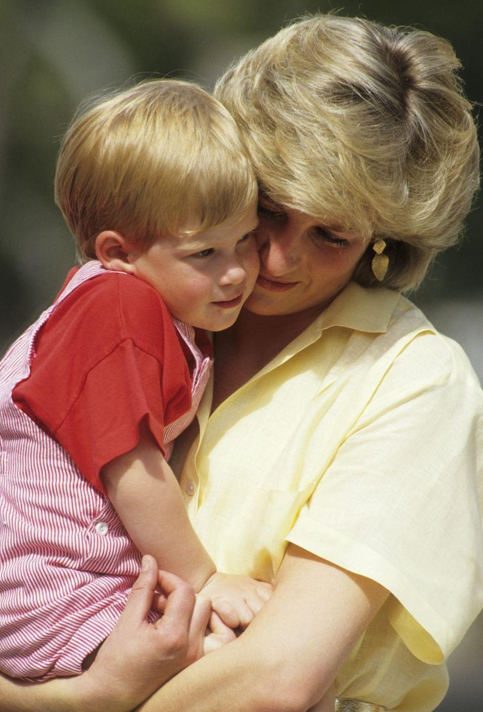 """<p>Princess Diana holds her nearly 3-year-old son, Prince Harry, while on holiday in Majorca, Spain in August 1987. In the same HBO documentary released in 2017, Harry said he can still feel Diana's hugs. """"I miss that, I miss that feeling. I miss that part of a family, I miss having that mother...to be able to give you those hugs and give you that compassion that I think everybody needs.""""</p>"""