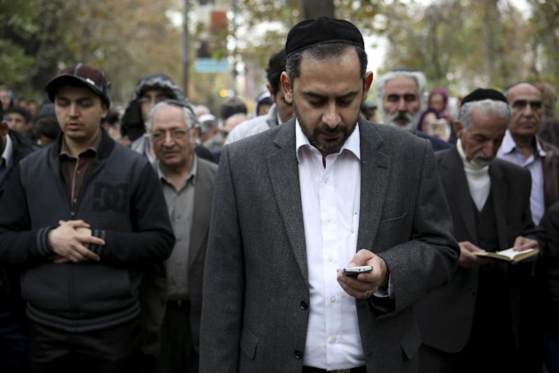 Iranian Jewish men pray in Hebrew during a gathering of Iran's Jewish community Iranian Jews hold a banner during a gathering of Iran's Jewish community outside a U.N. office in Tehran, Iran, Tuesday, Nov. 19, 2013. Hundreds of Iranians including university students and members of the country's Jewish community rallied Tuesday in support of the Islamic Republic's disputed nuclear program on the eve of the resumption of talks with world powers. (AP Photo/Ebrahim Noroozi)