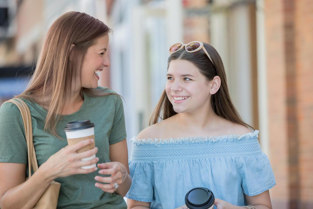 Mother laughing while walking with her teenage daughter at outdoor shopping mall. Caucasian mid adult woman and her teenage child are holding coffee cups and wearing casual clothing.
