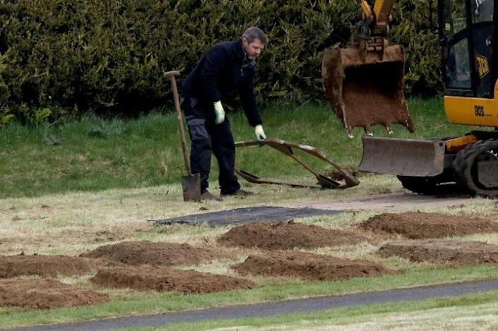 Workmen pre-dig graves at Sixmile Cemetery in Antrim, near Belfast, in Northern Ireland on April 2, 2020 (AFP Photo/Paul Faith)