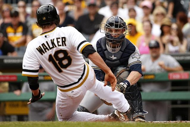 Pittsburgh Pirates' Neil Walker (18) is tagged out by Milwaukee Brewers catcher Jonathan Lucroy during the second inning of a baseball game in Pittsburgh Sunday, June 8, 2014. Walker was attempting to score from third on a single to right field by Pirate's Gaby Sanchez. (AP Photo/Gene J. Puskar)