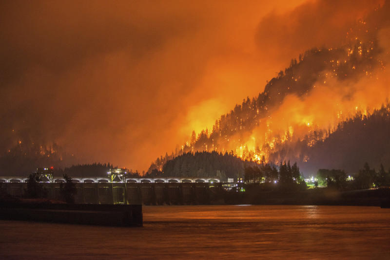 This Monday, Sept. 4, 2017, photo provided by KATU-TV shows a wildfire as seen from near Stevenson Wash., across the Columbia River, burning in the Columbia River Gorge above the Bonneville Dam near Cascade Locks, Ore. A lengthy stretch of highway Interstate 84 remains closed Tuesday, Sept. 5, as crews battle the growing wildfire that has also caused evacuations and sparked blazes across the Columbia River in Washington state. (Tristan Fortsch/KATU-TV via AP)